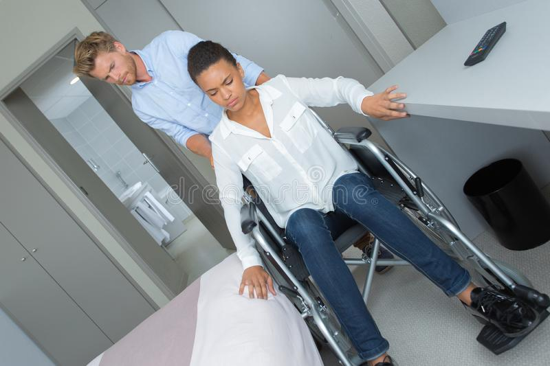 Young man with sad girl in wheelchair at home stock images