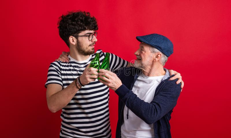 Young man and senior father with bottles in a studio on red background. royalty free stock photography