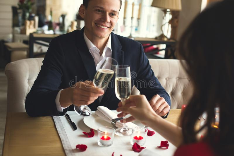 Young couple having romantic dinner in the restaurant drinking champagne cheers filter. Young men smiling close-up and women having romantic dinner in the stock photo