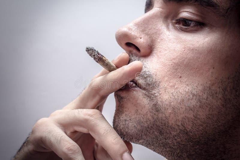 Young men smoking. Profile of a person smoking stock image