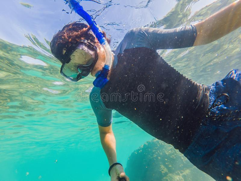 Young men snorkeling exploring underwater coral reef landscape background in the deep blue ocean with colorful fish and royalty free stock photography