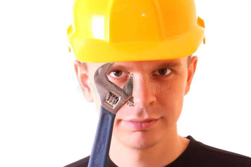 Young men with spanner. Handsome young men in a yellow building helmet and spanner in the hand isolated on white royalty free stock photos