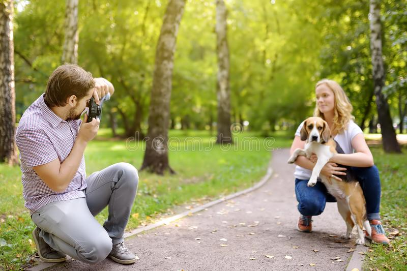 Young man take a shot beautiful woman with dog in sunny summer park. Date or walking stock photos