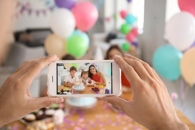 Young man taking photo of family while celebrating daughter's birthday at home royalty free stock images