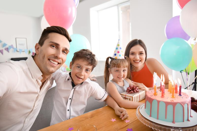 Young man taking selfie with family while celebrating daughter's birthday at home royalty free stock photo