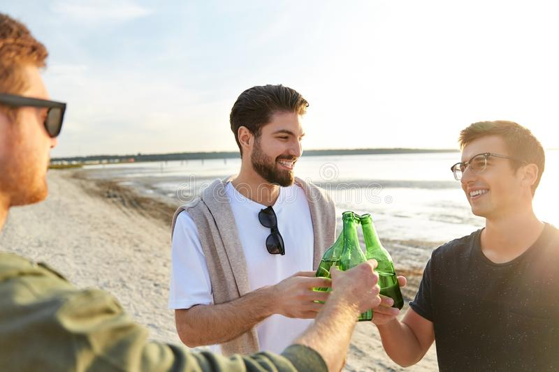 Young men toasting non alcoholic beer on beach royalty free stock photography