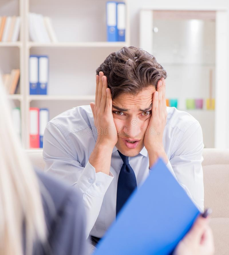 Young man visiting psychiatrist doctor for consultation. The young men visiting psychiatrist doctor for consultation royalty free stock image