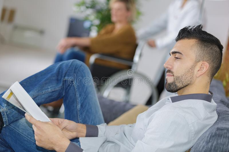 Young man waiting for doctor in hospital lobby. Young men waiting for the doctor in hospital lobby royalty free stock photography