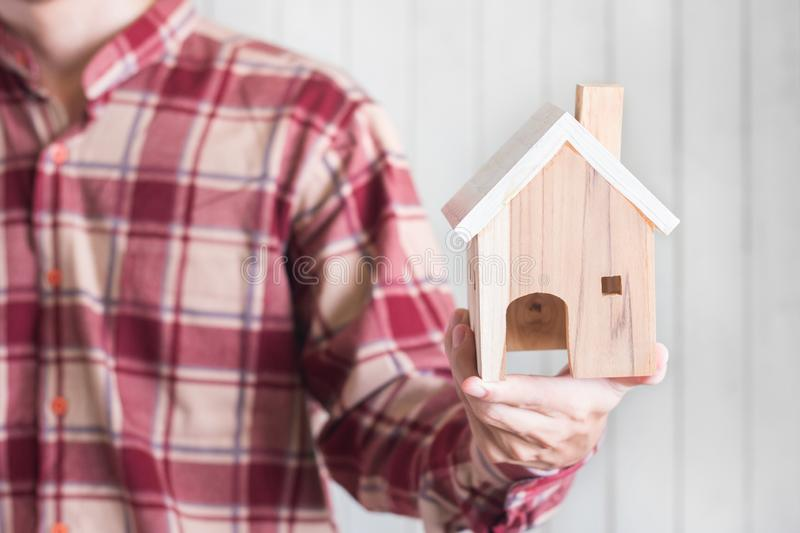 Young men wear red gingham shirt holding Miniature house model on white wood background, Property investment concept stock images