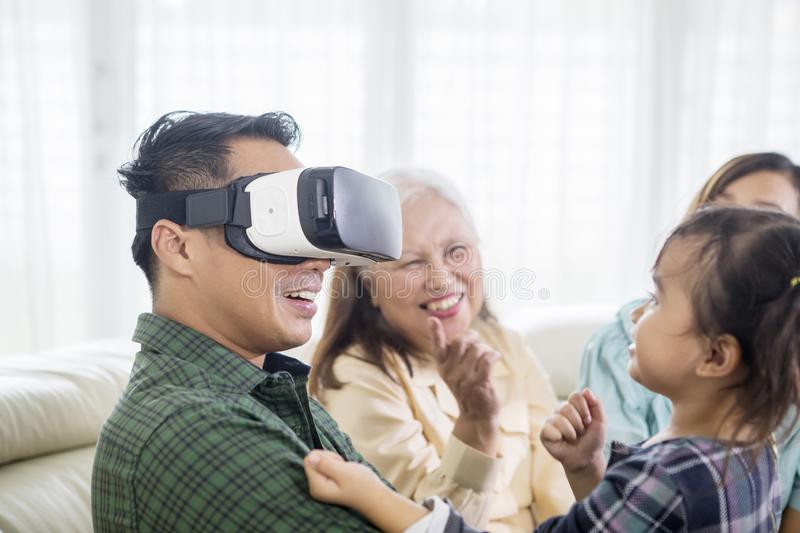Young man wearing VR headset with his family royalty free stock image
