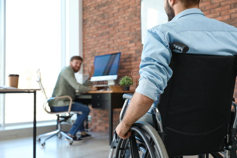 Young man in wheelchair with colleague at office. Young men in wheelchair with colleague at office, closeup stock images