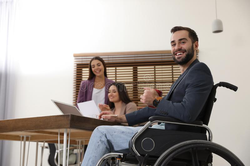 Young man in wheelchair with colleagues royalty free stock image