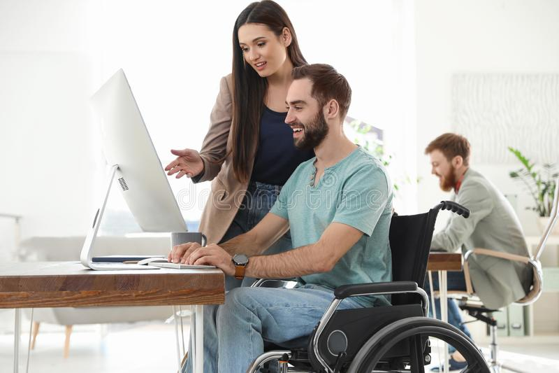 Young man in wheelchair with colleagues royalty free stock photos