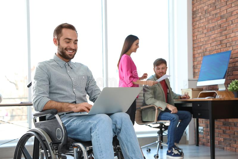 Young man in wheelchair with laptop and his colleagues. Young men in wheelchair with laptop and his colleagues at office royalty free stock photos