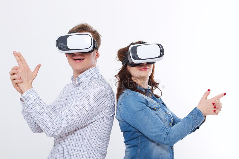Young man and woman in casual clothes in virtual goggles, vr isolated on white background. Technology and innovation concept. royalty free stock image