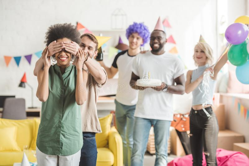 Young men and women covering eyes of young female friend and greeting her with birthday cake. On surprise party royalty free stock photography