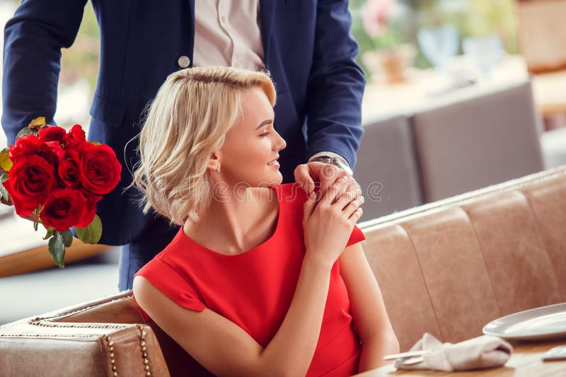 Young couple on date in restaurant man standing with bouquet behind sitting woman holding his hand cheerful royalty free stock photos