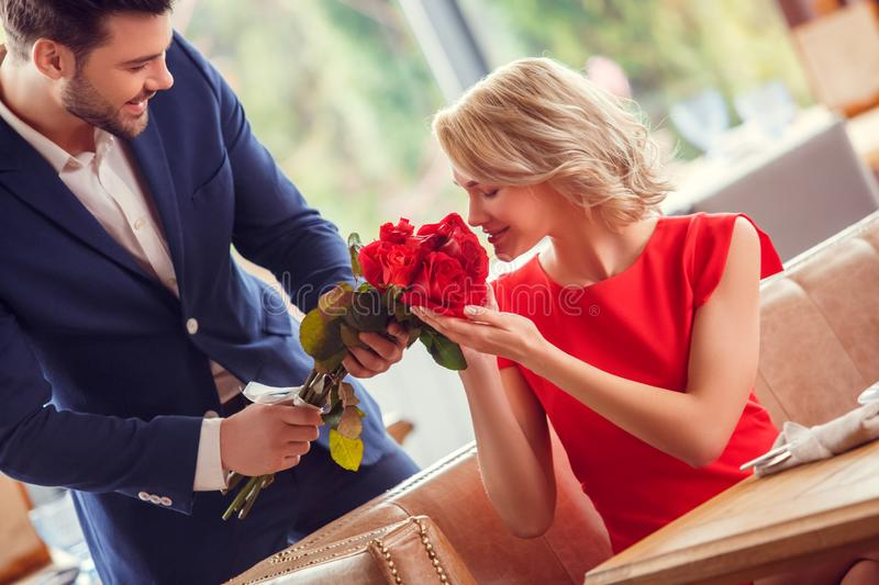 Young couple on date in restaurant man standing cheerful giving bouquet to woman sitting smelling buds happy stock photo
