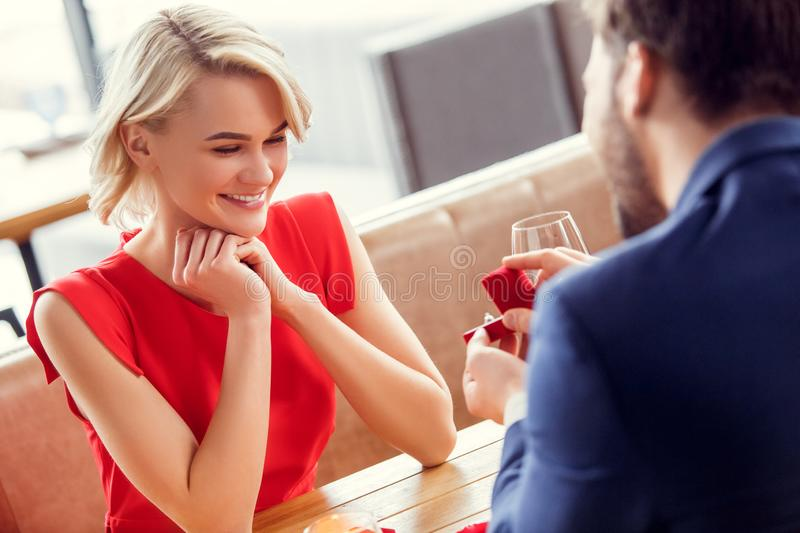 Young couple on date in restaurant sitting woman looking cheerful at proposal ring stock image