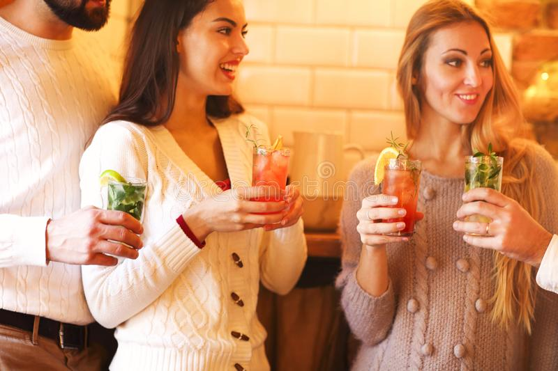 Young men and women drinking cocktail at party. Close up stock photos