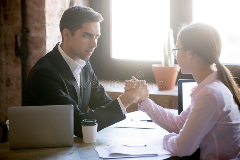 Man and woman are engaged in arm wrestling. Young men and women are engaged in arm wrestling, deciding who is stronger at work. Businessman and businesswoman stock photo