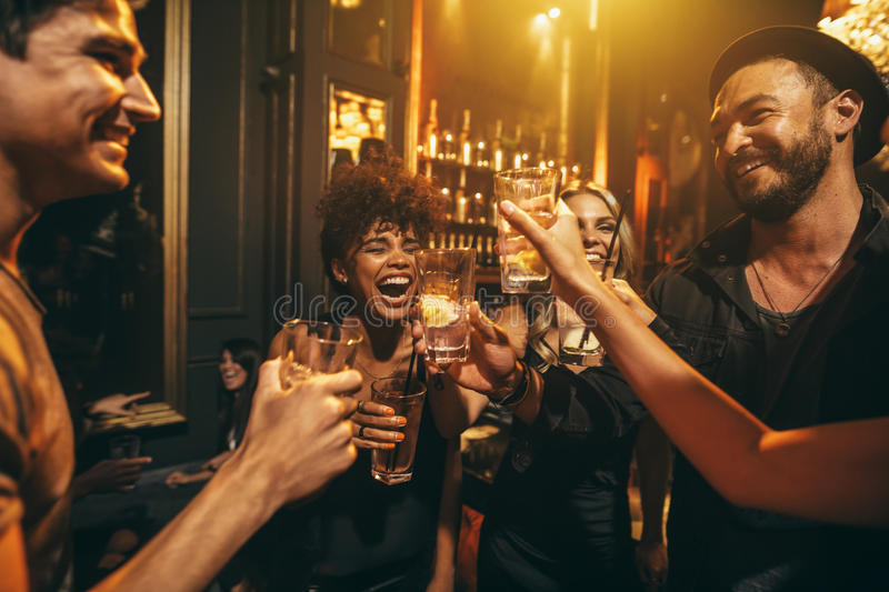 Young men and women enjoying a party. Shot of young men and women enjoying a party. Group of friends having drinks at nightclub stock photos