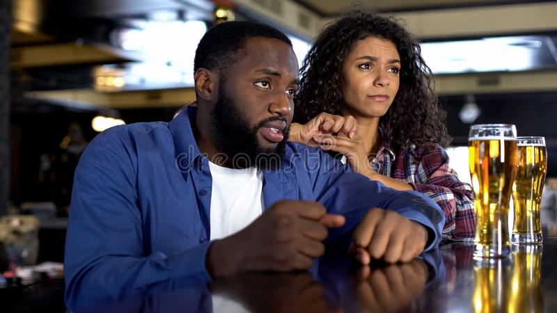 Young man and woman feeling disappointed by game result, fans rooting in bar royalty free stock photography