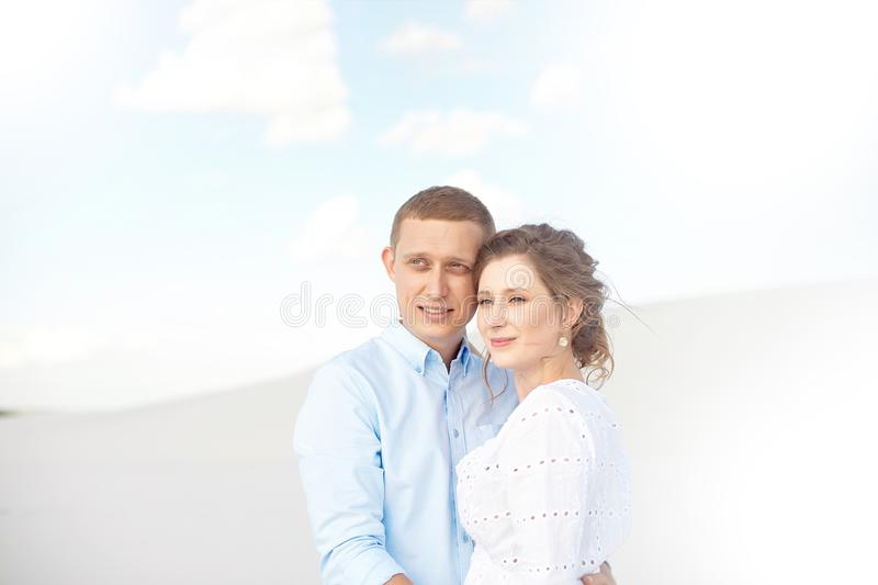 Young man and woman hugging on a background of white sand, dunes. Love story in the void. stock photo