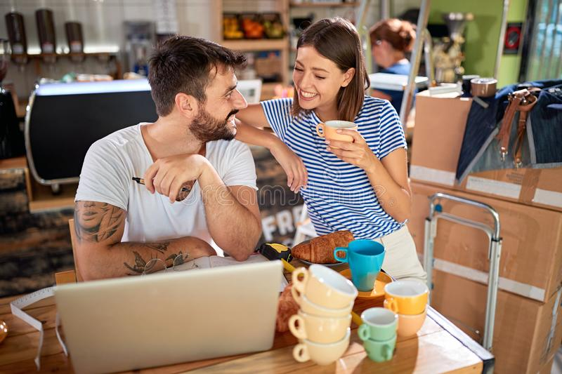 Man and woman partners standing in their new coffee shop and working to open. Young men and women partners standing in their new coffee shop and working to open royalty free stock photos