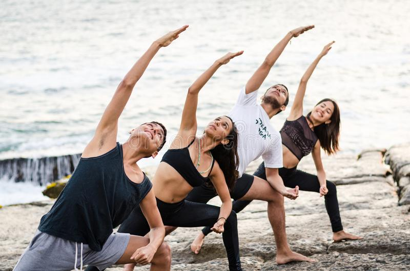 Young men and women practice balance asanas on Summer yoga session on a beautiful golden beach of Lima - Peru. On a yoga tour, Fulhadhoo, Extended Side Angle royalty free stock images