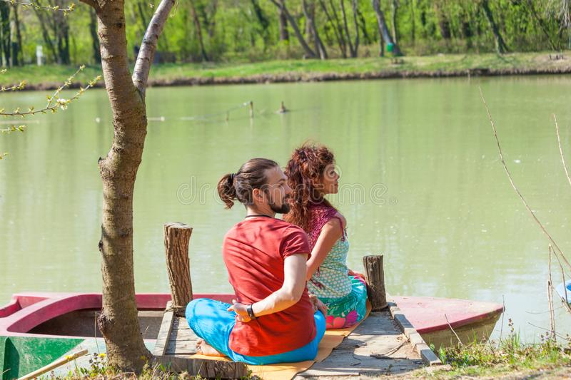 Young man and woman practice yoga outdoor by the lake sunny summer day stock images