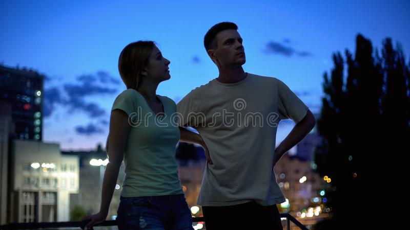Young man and woman seriously talking, evening leisure time in city, friends royalty free stock photography