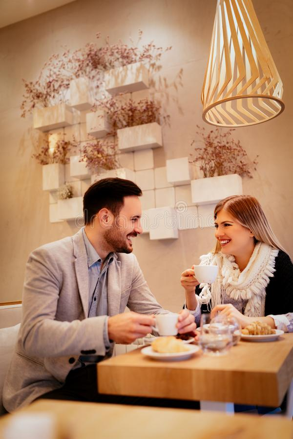 Couple In A Cafe. Young men and young women sitting at cafe and talking with smile. They drinking coffee and having breakfast stock image