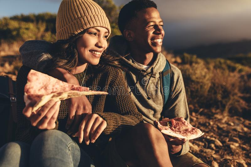 Hiker couple relaxing and admiring the view. Young men and women sitting on mountain trail eating pizza and looking at the view. Couple on hiking trip eating stock photo