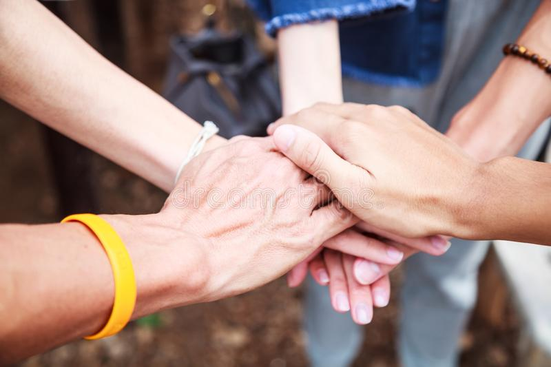 Young men and women standing and stacking hands in a meeting on natural ground background at outdoor outing. Teamwork, diversity, royalty free stock photo