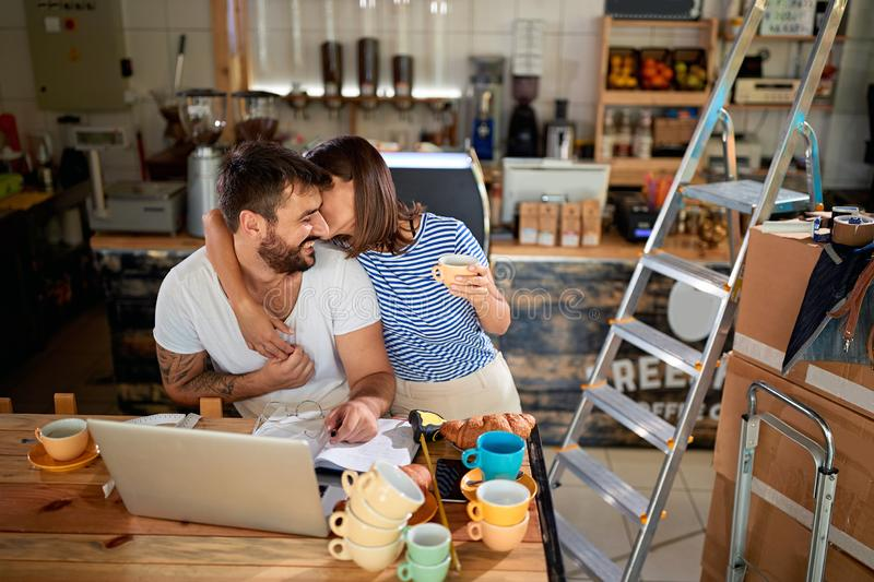 Man and woman standing in their new coffee shop and working to open. Young men and women standing in their new coffee shop and working to open stock image