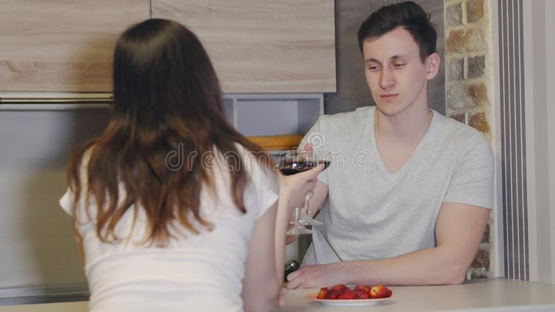 Young man and woman at a table with wine and strawberries. Romantic evening. Young men and women at a table with wine and strawberries. Romantic evening stock photos