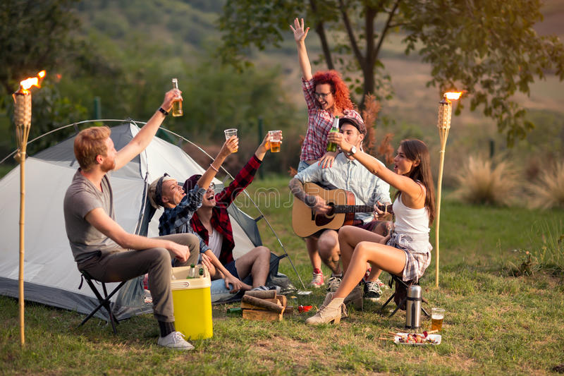 Young men and women toasting with beer on sunset in nature. Cheerful young men and women toasting with beer on sunset in nature stock photo