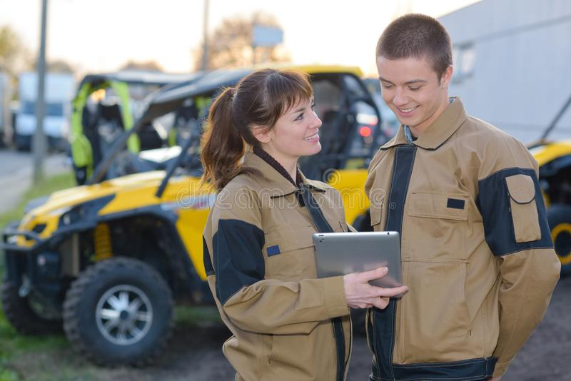 Young man and woman in uniform outdoors with tablet. Young men and women in uniform outdoors with tablet uniform royalty free stock images