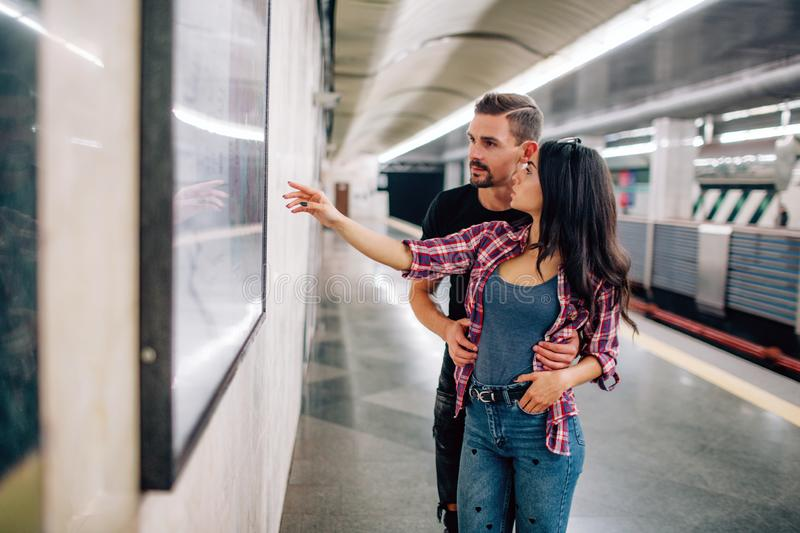 Young man and woman use underground. Couple in subway. Casual people in metropolitan. Young woman point on wall and. Young men and women use underground. Couple stock photo