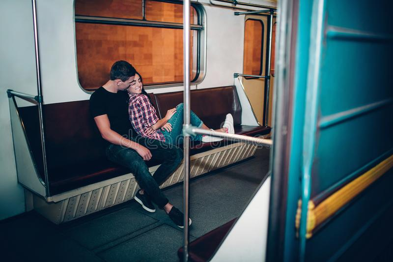 Young man and woman use underground. Couple in subway. Sitting on bench in metropolitan carriage. Relax and calm. Alone. Young men and women use underground stock photos