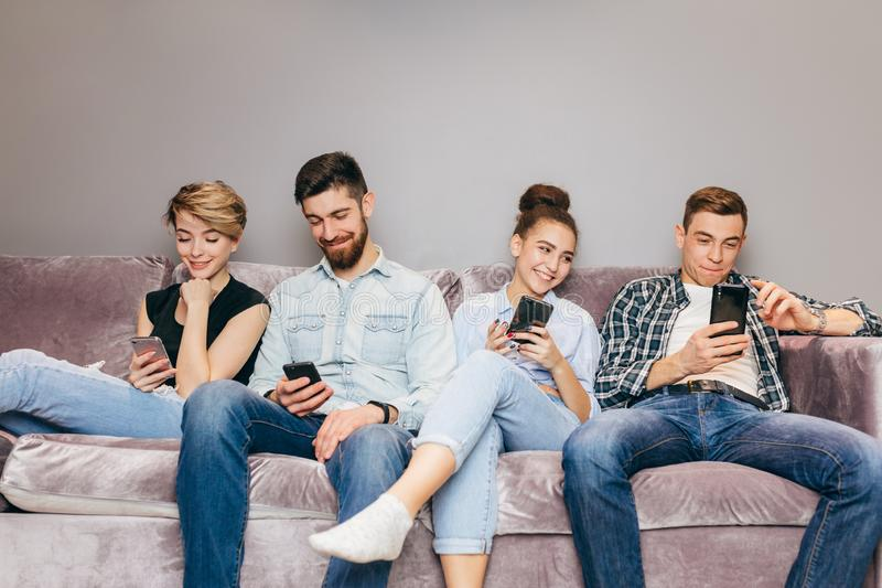 Young men and women are wasting their time. students are browsing the Net. Indoors. close up shot. mobile generation stock images