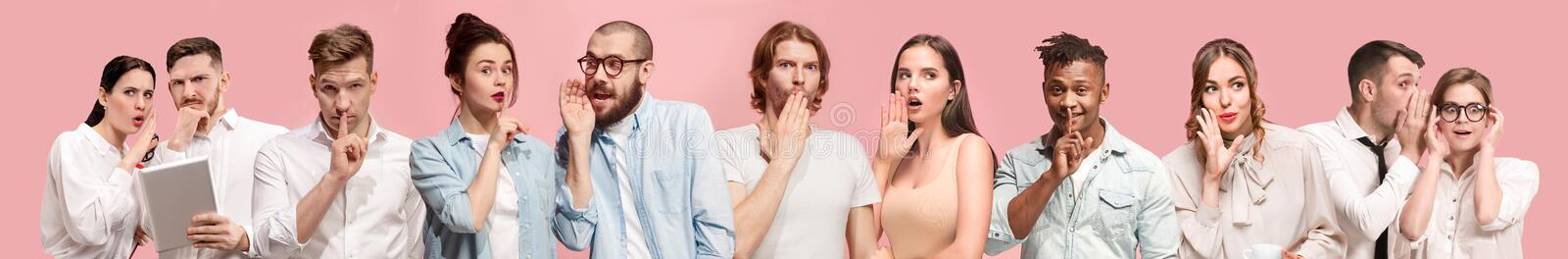 Young men and women whispering a secret on pink background royalty free stock photo