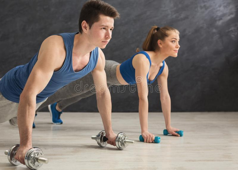 Couple making plank or push ups exercise indoors royalty free stock photos