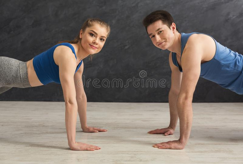 Couple making plank or push ups exercise indoors stock images