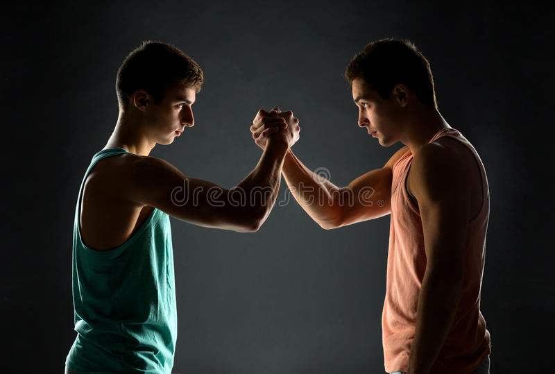 Young men wrestling. Sport, competition, strength and people concept - young men wrestling royalty free stock photo