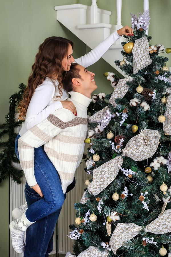Young man and young girl trim a Christmas tree together on the eve of the Christmas holidays. Young men and young girl trim a Christmas tree together on the eve royalty free stock image