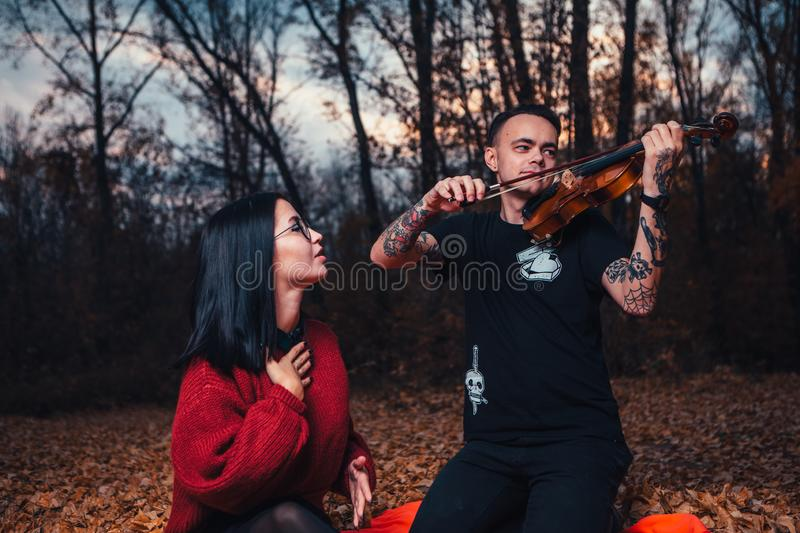 Young man play on violin and young woman are sitting on a plaid in an autumn forest stock photography