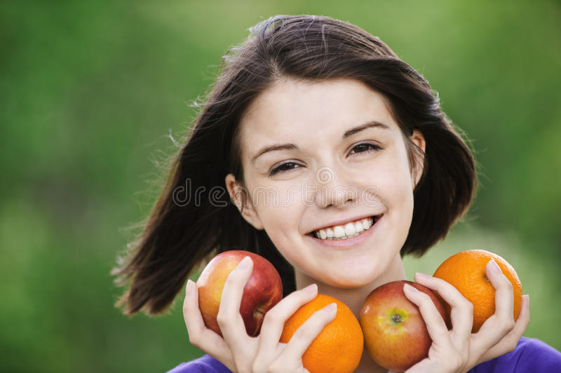 Young merry woman holding fruits stock photography