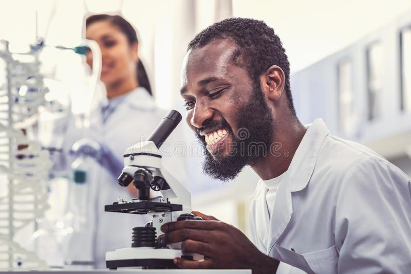 Young microbiologist feeling extremely happy. Extremely happy. Young promising microbiologist feeling extremely happy while making sensational research royalty free stock images